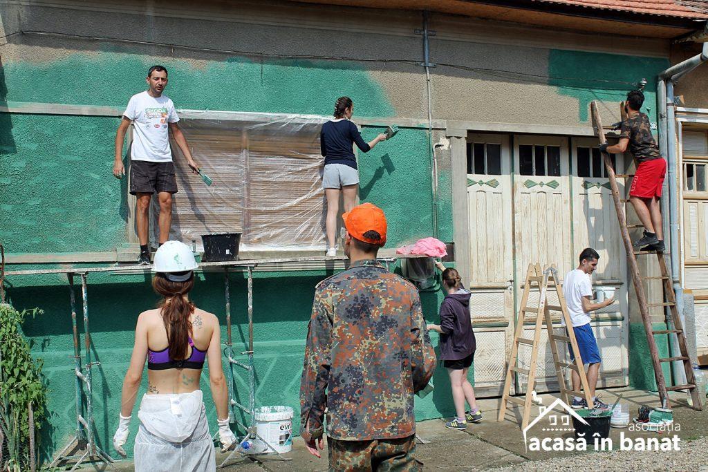 Echipă de voluntari zugrăvind fațada unei case din satul Eftimei Murgu, județul Caraș-Severin