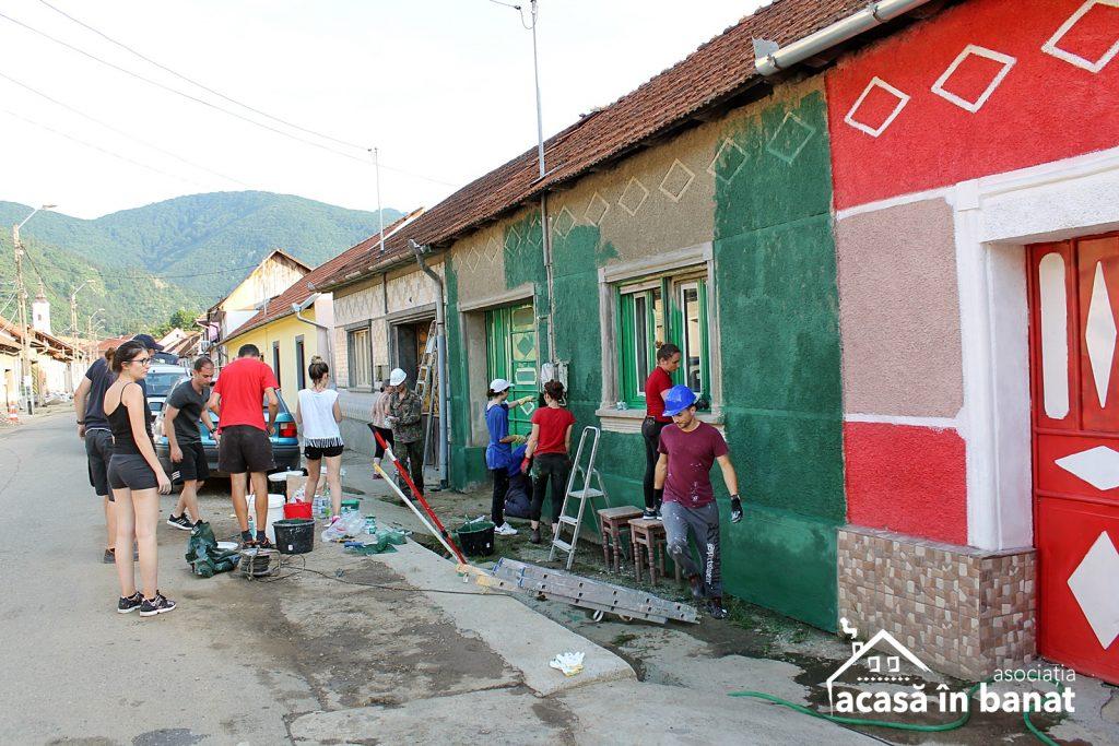 Voluntari renovând fațada unei case din Eftimie Murgu, județul Caraș-Severin